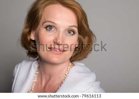Smiling middle aged woman with a gray background. - stock photo