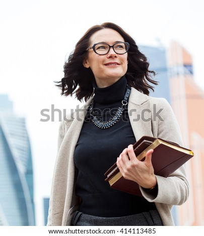 smiling middle-aged woman with glasses on his face, and with books in their hands on open air - stock photo