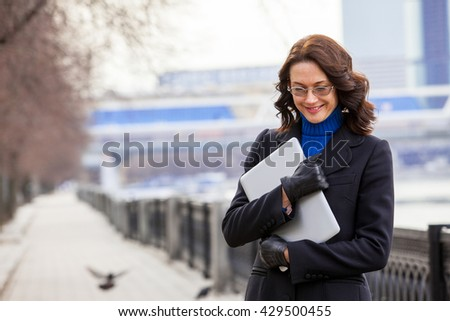 smiling middle aged woman with laptop outdoor