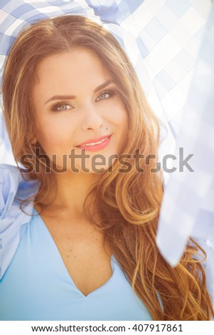Smiling middle-aged woman with red lips in the city. Attractive model in blue shirt looking at the camera and enjoying her daytime. Toned image.