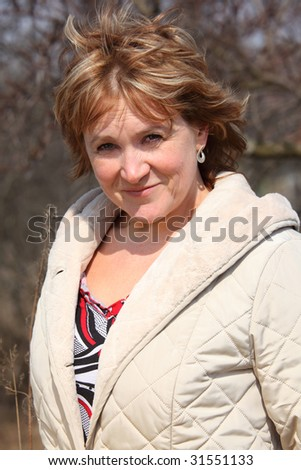 Smiling middleaged woman outdoor - stock photo