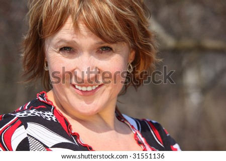 Smiling middleaged woman outdoor closeup - stock photo