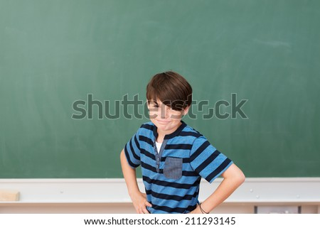 Smiling mischievous little schoolboy standing in front of the blackboard with his hands on his hips giving the camera a cheeky grin - stock photo