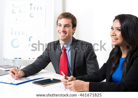 Smiling mixed race business people in meeting room