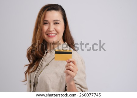 Smiling mixed-race woman showing credit card, focus on foreground