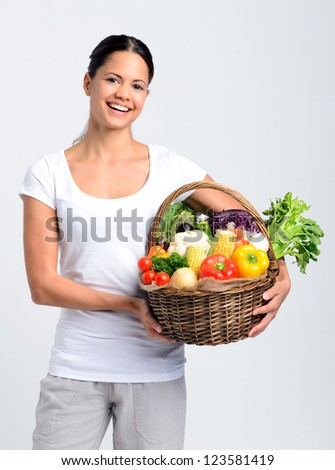 Smiling mixed race young woman holding a basket full of fresh organic vegetables on grey background, promoting healthy diet and lifestyle - stock photo