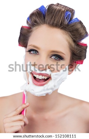 Smiling model in hair curlers posing while shaving on white background - stock photo