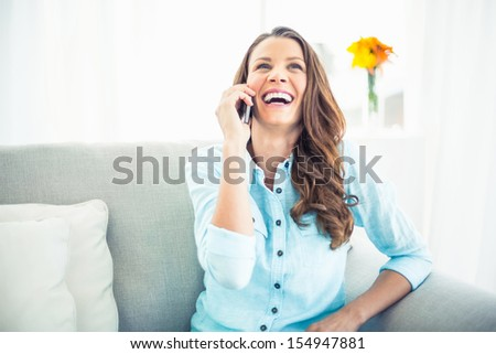 Smiling model sitting on cosy couch in bright living room having a phone call - stock photo