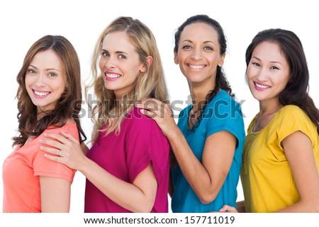 Smiling models posing with colorful t shirts with hands on shoulders on white background - stock photo