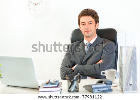 Smiling modern business man with crossed arms on chest sitting at office desk