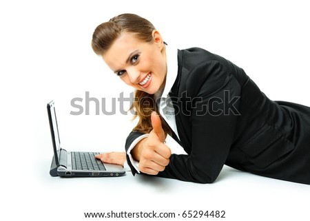 Smiling modern business woman with laptop and showing thumbs up gesture