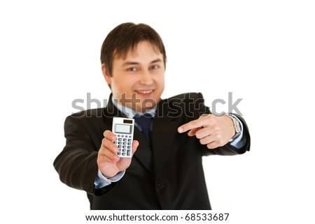 Smiling modern businessman pointing finger on calculator isolated on white - stock photo