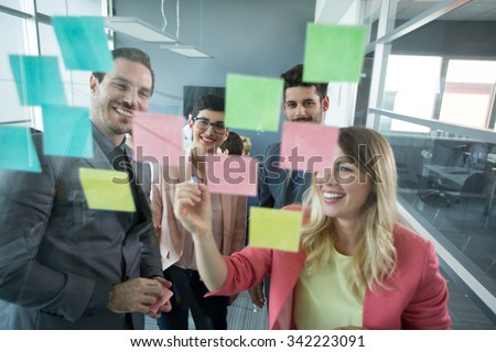 Smiling modern partners looking at sticky notes   - stock photo
