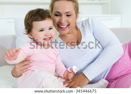Smiling mom and baby cuddling on the sofa.Shallow doff - stock photo