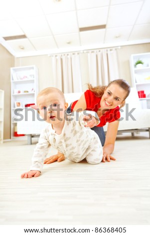 Smiling mommy playing with creeping on floor baby - stock photo