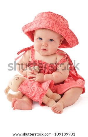 Smiling 6 month old baby girl sits holding a stuffed toy bunny rabbit. Baby's strawberry pink floral hat and sun dress match the toy. Vertical, copy space, isolated on white. - stock photo