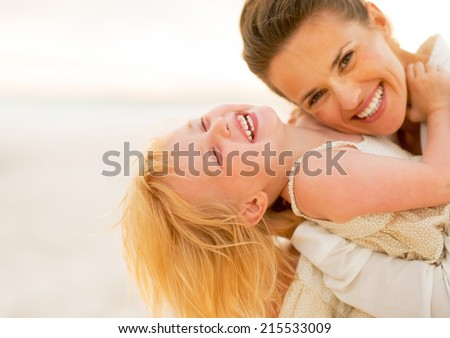 Smiling mother and baby girl having fun time on the beach in the evening - stock photo
