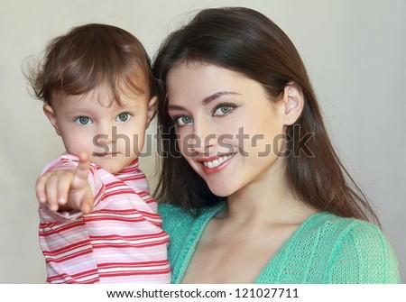 Smiling mother and baby girl showing finger on something with fun look. Closeup isolated portrait - stock photo