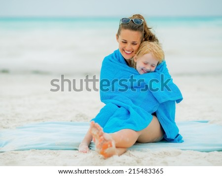 Smiling mother and baby girl wrapped in towel sitting on beach