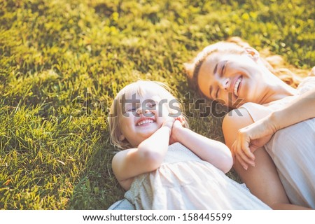 Smiling mother and baby laying on meadow - stock photo