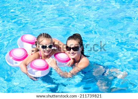 Smiling mother and daughter floating in the swimming pool  - stock photo
