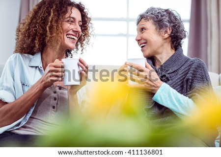 Smiling mother and daughter holding coffee mugs while discussing at home - stock photo