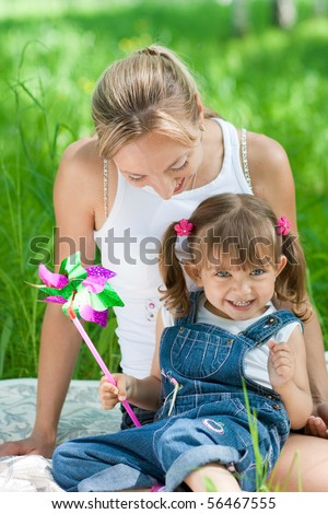 Smiling mother and daughter in jeans with colorful toy outdoor - stock photo
