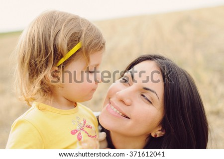 smiling mother and daughter looking at each other