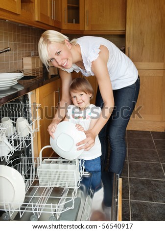 Smiling mother and daughter looking in the camera standing in the kitchen - stock photo