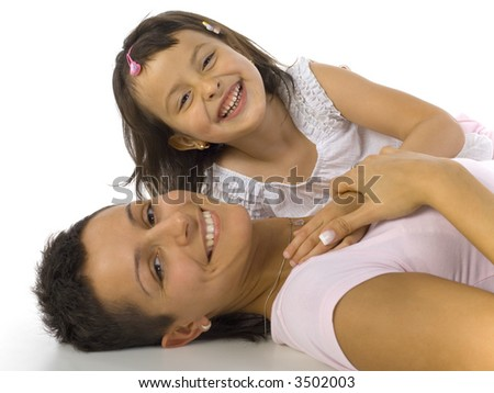 Smiling mother and daughter lying on the floor. Looking at camera, white background - stock photo