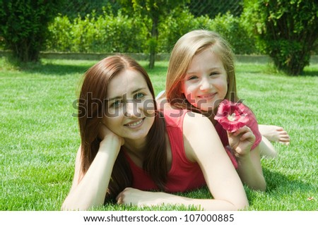 Smiling mother and daughter on the  grass