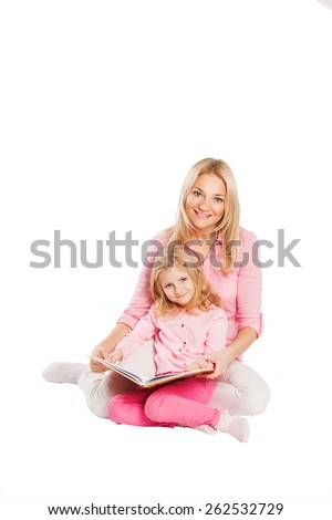 Smiling mother and daughter reading on white background. - stock photo