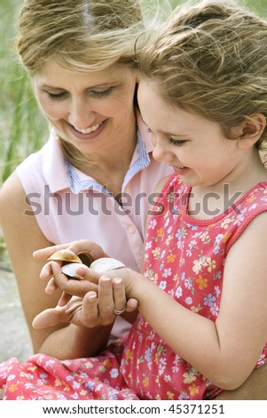 Smiling mother and daughter sit on sand examining seashells together. Vertical shot. - stock photo