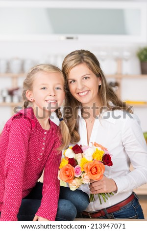 Smiling mother and daughter with a bunch of colourful fresh cut roses posing close together smiling at the camera - stock photo