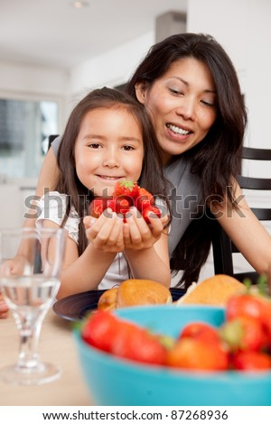 Smiling mother and daughter with fresh picked strawberries - stock photo