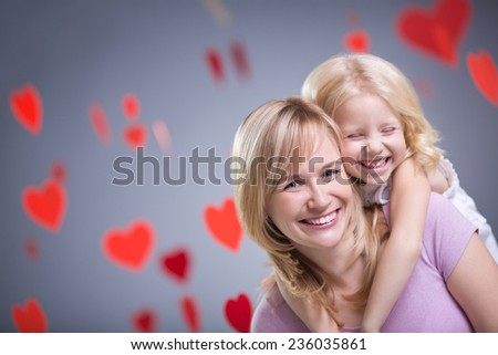 Smiling mother and daughter with hearts - stock photo