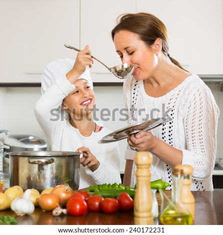Smiling mother and her cheerful daughter preparing soup at kitchen  - stock photo