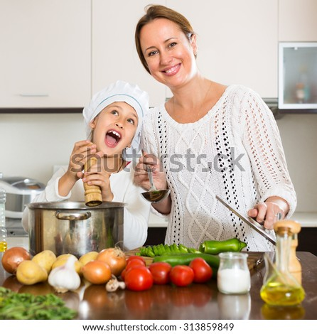 Smiling mother and her cheerful daughter preparing soup together at kitchen - stock photo