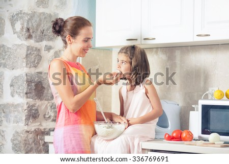 Smiling mother and her cute little daughter preparing and eating healthy meal in the kitchen - stock photo