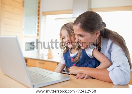Smiling mother and her daughter using a laptop in their kitchen - stock photo