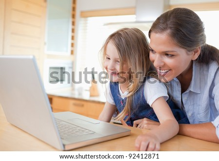 Smiling mother and her daughter using a notebook in their kitchen - stock photo