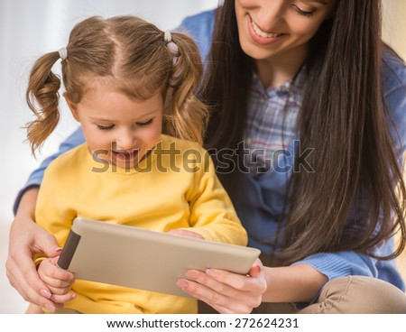 Smiling mother and her little daughter are looking at something in tablet and spending time funny. - stock photo