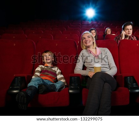 Smiling mother and her son in cinema with other people behind them. - stock photo