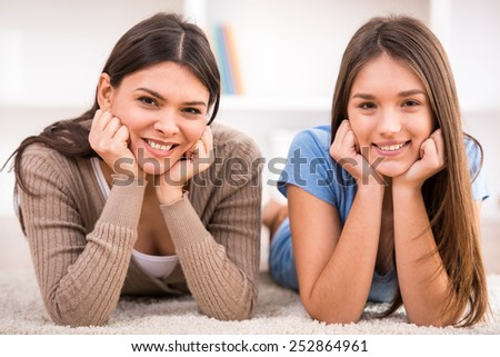 Smiling mother and her teen daughter are lying on the floor and looking at the camera. - stock photo