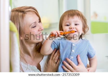 smiling mother and kid son brushing teeth in bathroom - stock photo