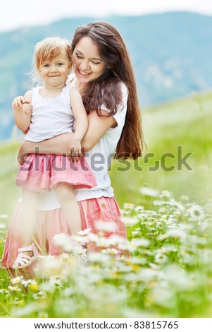 Smiling mother and little daughter on nature. Happy people outdoors - stock photo