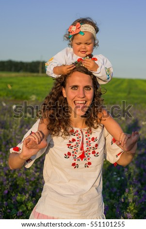Smiling mother and little daughter on nature in a field of poppies, girl is holding flowers. Happy people outdoors