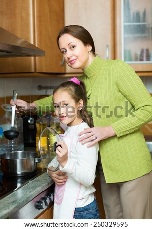 Smiling mother and little daughter preparing soup together at domestic kitchen. Focus on girl