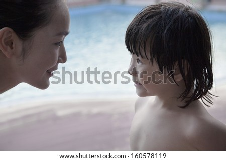 Smiling mother and son face to face by pool - stock photo