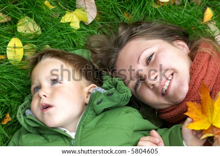 Smiling mother and son on the grass covered with fallen leaves - stock photo